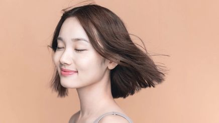 Asian girl with short hair blowing in the wind against brown background