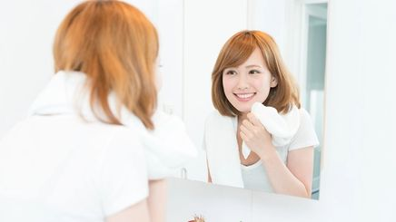 An Asian woman with short hair smiling at a mirror and touching her face