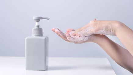 A person washing hands using liquid soap