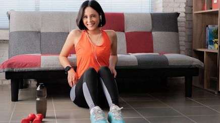 A smiling Asian woman in a bob wearing workout clothes