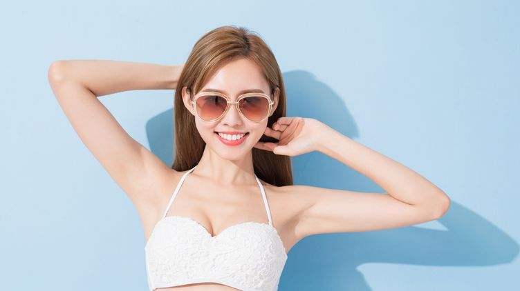 Woman in white top and sunglasses showing underarms