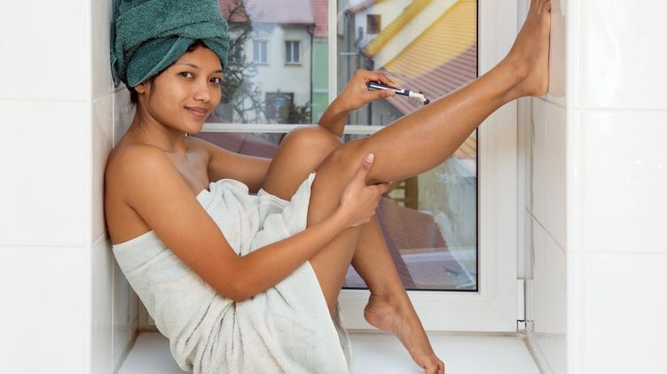 Asian woman with towel shaving