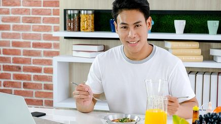 Young Asian man eating a healthy breakfast while looking at his laptop