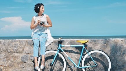 Asian woman with a bicycle outdoors