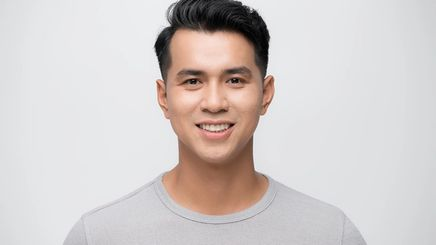 A handsome Asian man smiling and wearing a plain gray t-shirt