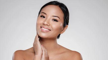 An Asian woman touching her face
