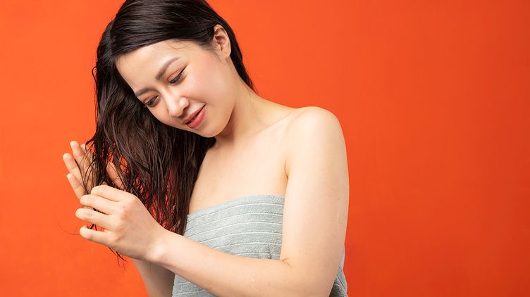 Asian woman touching wet hair