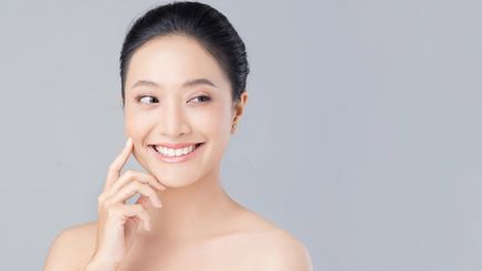 Asian woman with clear skin touching her face with finger.