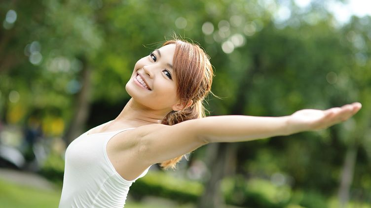 A beautiful Asian woman in a white tank tap raising her arms outdoors