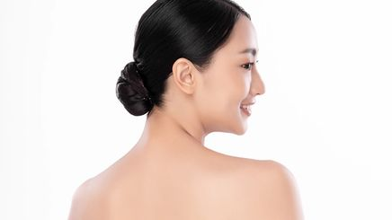 An Asian woman wearing a low bun and showing her upper back
