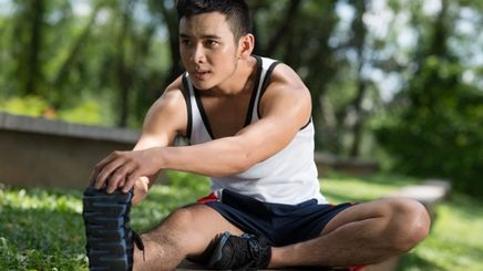 Young Asian man doing leg stretches in the park