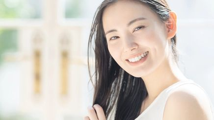 Asian woman applying hair treatment