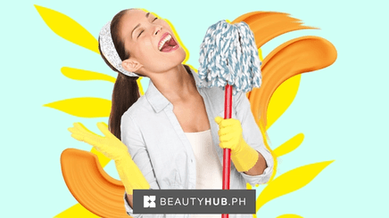 An Asian woman wearing a bandana and gloves using her mop as a mic