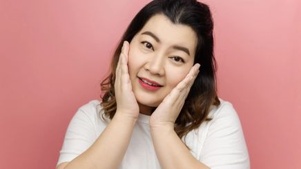Asian woman smiling while touching face