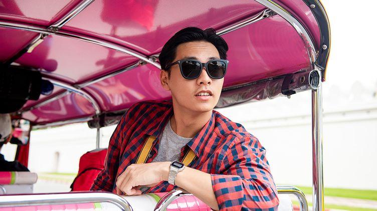 Asian man wearing sunglasses riding public transportation