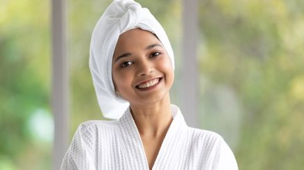 A woman wearing a towel on her head and robe.