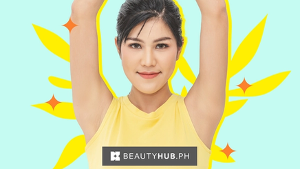A woman in a yellow shirt with both arms raised