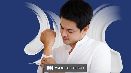 An Asian man putting on a white formal shirt