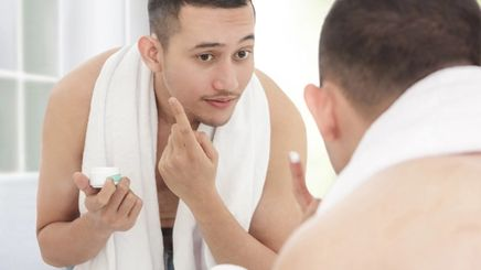 Handsome Asian man applying cream on his face while looking at himself in the mirror