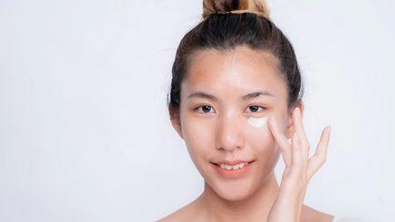 Asian woman applying concealer under her eyes