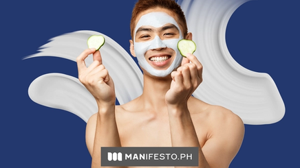 A smiling man holding cucumbers and wearing a face mask