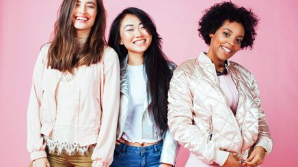 Three women with different skin tones posing against a pink background