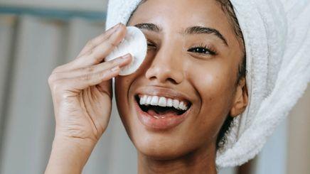 A beautiful woman applying face toner.