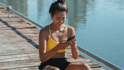 Sweaty Asian woman sitting on a wooden bridge with phone