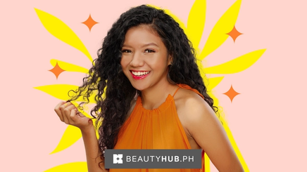 An Asian woman with red lipstick and curly hair