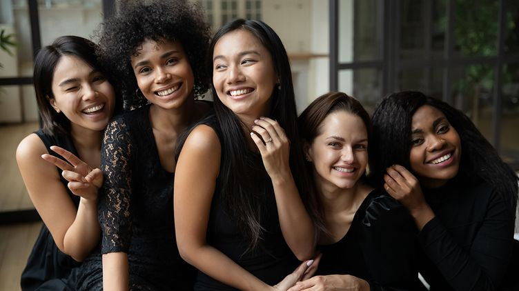 Five women of different ethnicities posing in their black dress