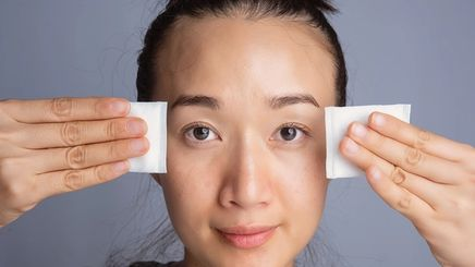 Asian woman cleanses skin with cotton pad