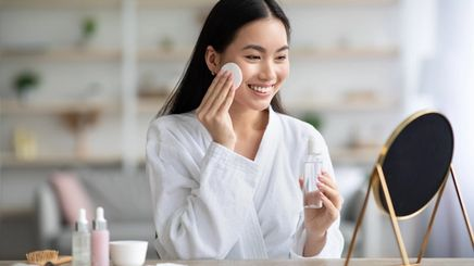 Asian woman cleansing her face with a cotton pad