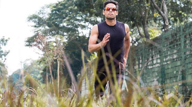Fit Asian man in sunglasses running outdoors