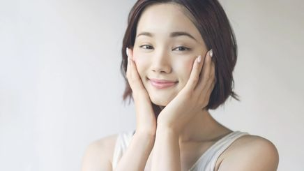 A young Asian woman touching her face