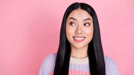 An Asian woman with long black hair standing in front of a pink background