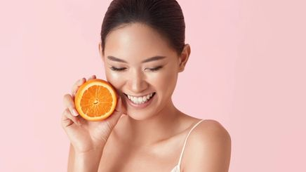 Smiling Asian woman holding half an orange