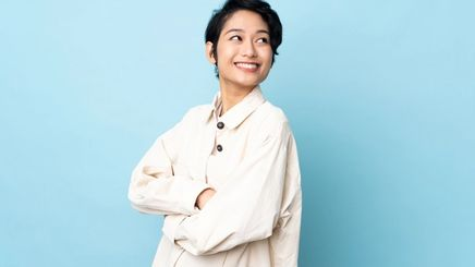 An Asian woman with androgynous hair cut wearing a white shirt against a blue background