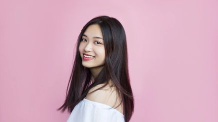 An Asian woman with long hair and white top smiling