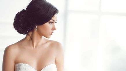 A beautiful bride in chignon hairstyle looking out the window