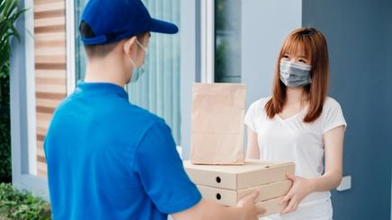 Woman with facial mask receiving packages from delivery man.