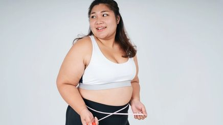 A plus-size woman in a white sports bra with a tape measure