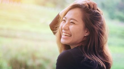 An Asian woman touching her hair