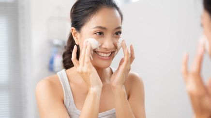 Woman looking at the mirror while washing her face.