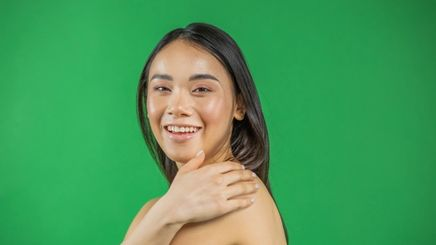 A woman with glowing skin touching her shoulder