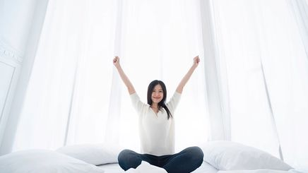 Happy Asian woman on a bed