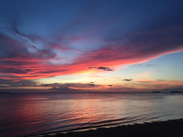 Sunset over the ocean in Koh Phangan, Thailand with bright pink, orange, and yellow reflected on the water
