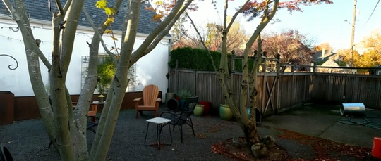 A picture of our backyard before we added anything. We have a few chairs in the middle of the yard, and we've got a fence that is old and kind of rotten. The backyard is covered in gravel and we have large cement pad as part of the patio that's next to the house.