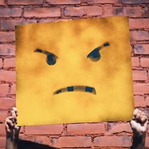 Someone holding a yellow sign that's painted with an angry face