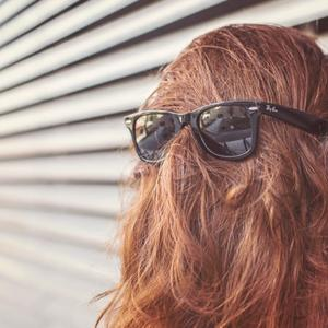 Person with hair covering their face and sunglasses over their hair