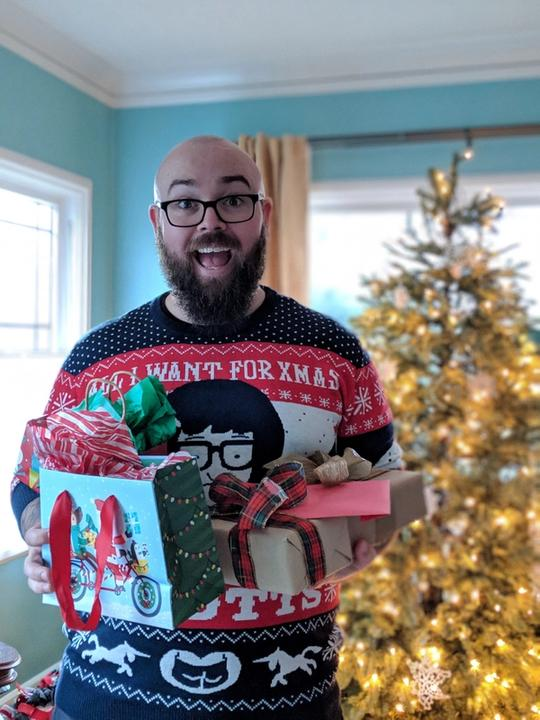 Jason standing in front of a Christmas tree holding several presents and smiling